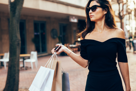 Stylish asia woman walking on the street with shopping bags. Beautiful female model outdoors in road after shopping. Stock Photo