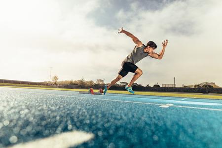 Runner die startblok gebruikt om zijn looppas op renbaan te beginnen. Atleet begint zijn sprint op een baan voor alle weersomstandigheden met behulp van startblok.