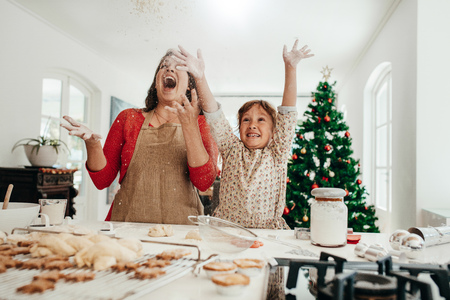 Happy mother and daughter in kitchen throwing flour in air while making cookies. Baked star cookies, muffins and gingerbread on kitchen table with decorated Christmas tree in the background.