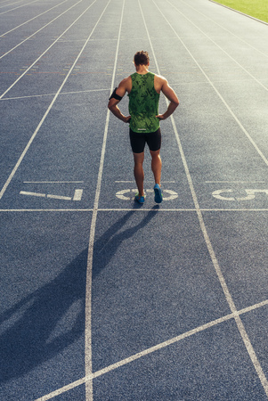 Rear view of an athlete standing on an all-weather running track. Runner standing at the start line with hands on waist. Фото со стока