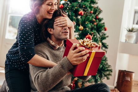 Couple spending happy moments while celebrating Christmas at home. Smiling young woman covering eyes of her partner while handing over a Christmas gift.