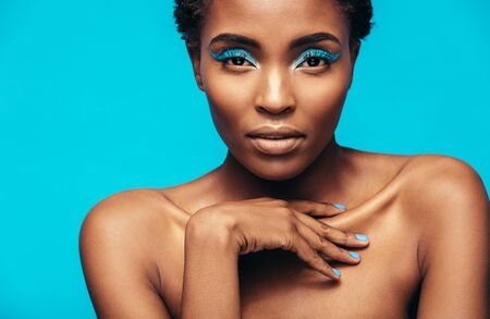 Close up of sensual african woman wearing vivid makeup against blue background. Female model with beautiful skin looking at camera. Stock Photo