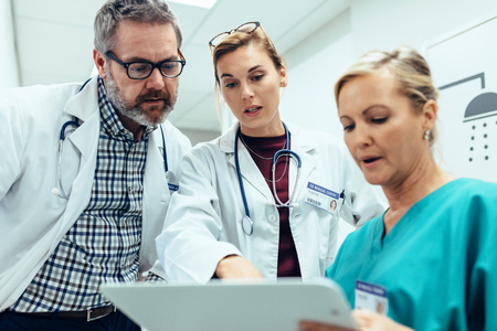 Medical staff discussing over medical reports. Healthcare professionals having discussion in hospital corridor. Stock Photo