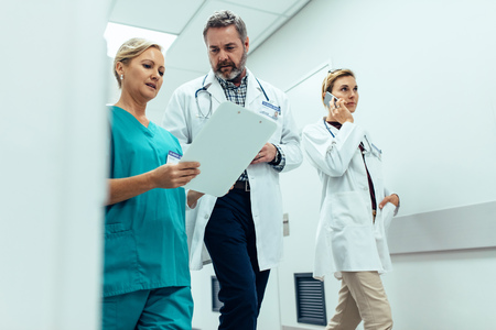 Busy hospital staff walking in hospital hallway discussing medical report. Three healthcare workers in hospital corridor.