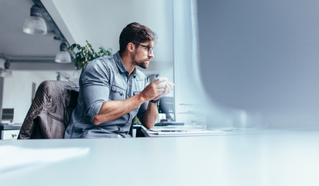 Businessman sitting in office with cup of coffee. Young man holding mug and looking away.