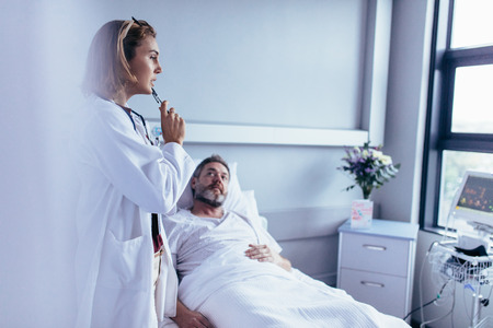 Physician in hospital room looking at patient monitoring device with sick man lying in bed. Doctor taking decision for treatment on hospitalised man.