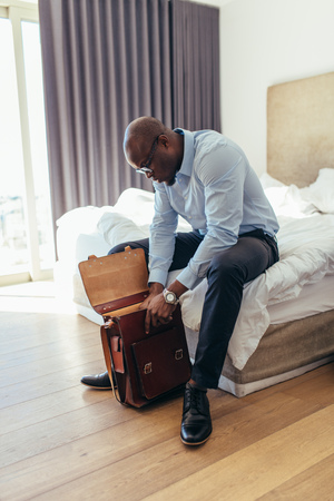 Businessman checking his bag sitting on bed. Man getting ready to go to office.