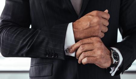 소매를 수정하는 정장 소송에서 사업가의 근접 촬영. 남성 손을 흰색 셔츠 커프스 슬리브 고정입니다.