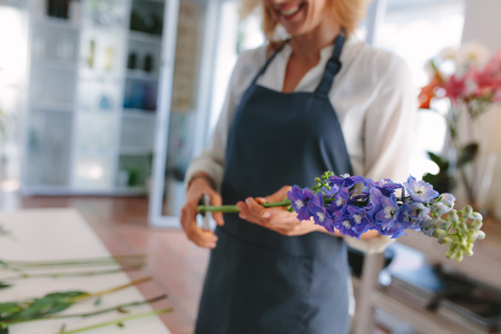 Female florist creating bouquet of flowers. Woman florist cutting flowers with scissors and designing bouquet at workshop. Focus on flowers.