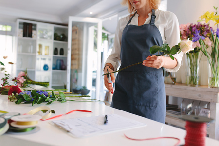 Skillful female florist creating bouquet of flowers. Young woman florist cutting flowers with scissors and designing bouquet on counter at workshop.