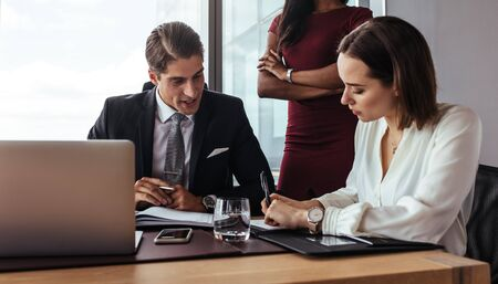 Business people working in team at office. Three people in office with businessman dictating to his assistant making notes while other female colleague standing by.