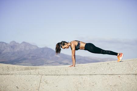 タフな若い女性が屋外での腕立て伏せ。女性の朝の運動フィットネス。 写真素材