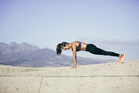 Tough young woman doing pushups outdoors. Fitness female exercising in morning. Stock Photo