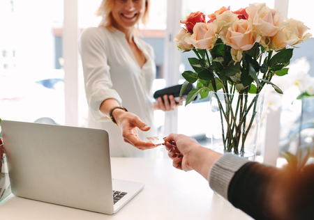 consumerism: Female florist taking credit card for payment from customer. Client paying for flowers with debit card. Cashless payments at flower shop. Focus on hands.
