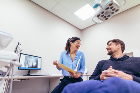 Happy dentist and patient at dental clinic. Smiling doctor and patient discussing report at dental clinic. Archivio Fotografico