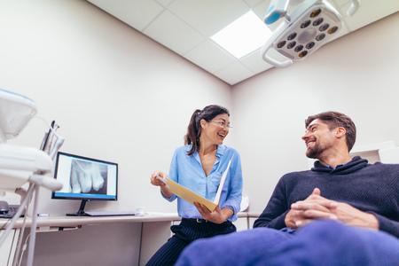 Glücklicher Zahnarzt und Patient an der zahnmedizinischen Klinik. Lächelnder behandelnder Bericht Doktors und des Patienten an der zahnmedizinischen Klinik. Standard-Bild - 90004935