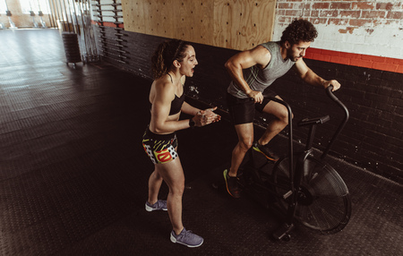 Personal trainer motivating man exercising on air bike in gym. Man doing intense workout on gym bike with female coach.