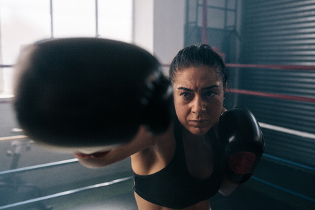 Boxer practicing her punches at a boxing studio. Close up of a female boxer punching inside a boxing ring.