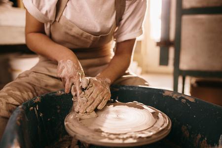 Woman flattening clay on pottery wheel in workshop. Craftswoman working on clay with flattening tool on pottery wheel. Stock Photo