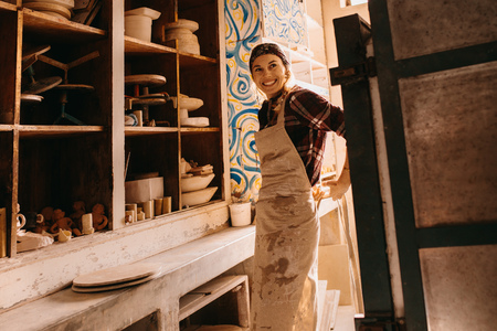 Smiling woman potter standing in her pottery workshop wearing an apron.