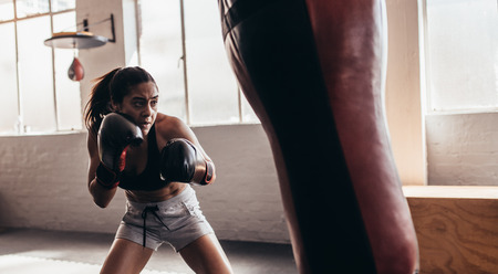 Female boxer hitting a huge punching bag at a boxing studio. Woman boxer training hard. Reklamní fotografie