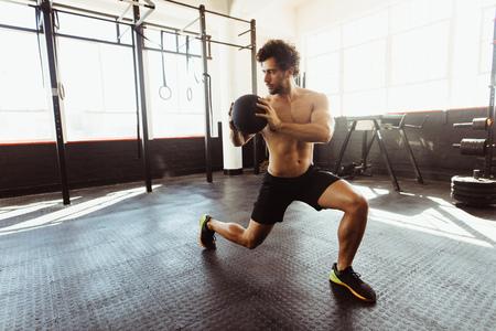 Treino de força e estabilidade do núcleo. Homem apto e muscular que exercita com a bola de medicina no gym.
