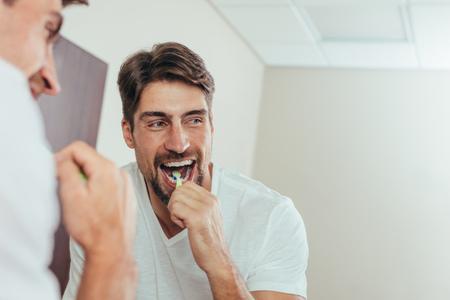 Man in the bathroom brushing teeth. Reflection of man in bathroom mirror while brushing teeth in morning. Stock Photo