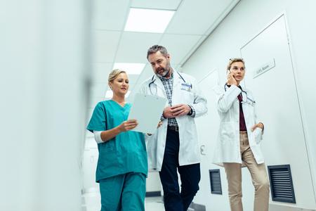 Doctors team walking in hospital corridor indoors. Emergency paramedic team in hospital hallway. 스톡 콘텐츠