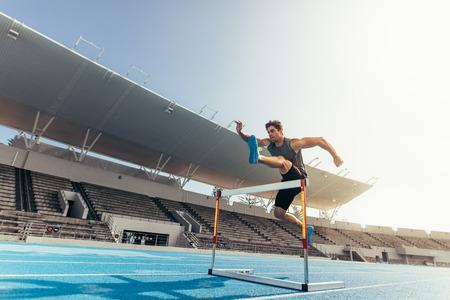 Biegacz przeskakujący przez przeszkodę podczas zawodów lekkoatletycznych. Sportowiec prowadzący wyścig przez płotki na stadionie. Zdjęcie Seryjne