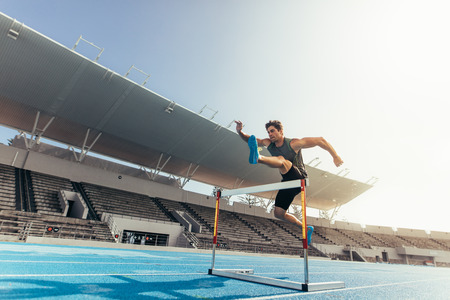 Runner jumping over an hurdle during track and field event. Athlete running a hurdle race in a stadium. Фото со стока