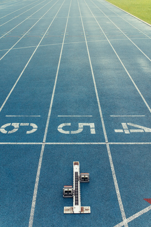 Starting block placed at the start line of a running track. Metal starting block isolated on a blue all-weather running track.