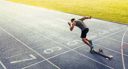 Rear view of an athlete starting his sprint on an all-weather running track. Runner using starting block to start his run on race track. Banco de Imagens - 90571802