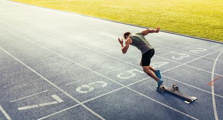 Widok z tyłu sportowca rozpoczynającego sprint na bieżni na każdą pogodę. Biegacz używa bloku startowego, aby rozpocząć swój bieg na torze wyścigowym.