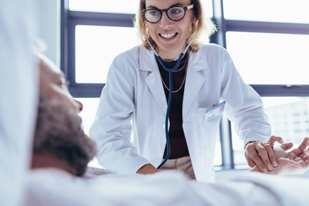 Happy female doctor examining male patient in hospital room. Medicine professional checking pulse of hospitalised man. Stock Photo