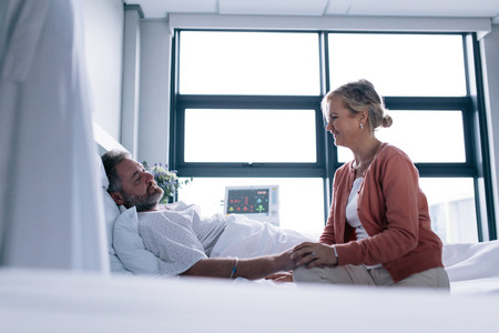 Woman visiting husband in hospital. Female talking with male patient lying in hospital bed.