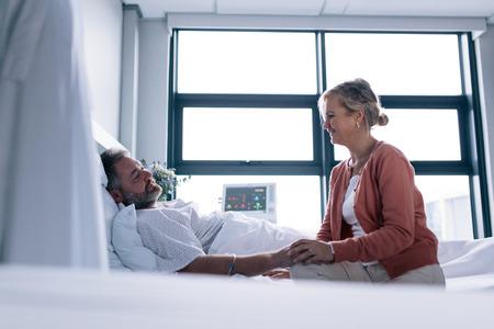 Vrouw bezoekende echtgenoot in het ziekenhuis. Wijfje dat met mannelijke patiënt spreekt die in het ziekenhuisbed ligt.