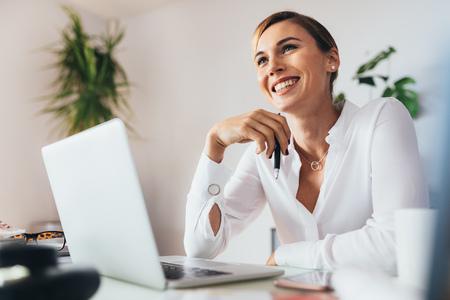 Lächelnde Geschäftsfrau , die an ihrem Schreibtisch im Büro sitzt . Frau , die einen Stift mit einem Laptop-Computer auf ihrem Schreibtisch hält