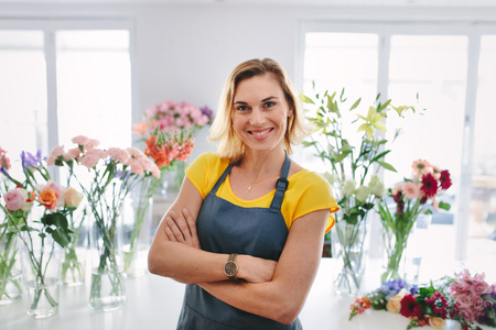 Positive flower shop owner looking at camera and smiling. Small business owner. Stock fotó