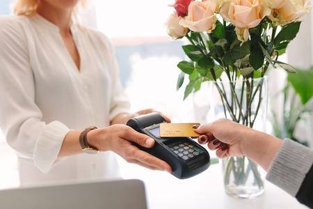 Mano del cliente que realiza el pago mediante tarjeta de crédito de tecnología nfc en la florería. Cliente que paga con tarjeta sin contacto en floristería Foto de archivo