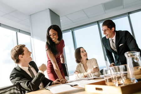 Group of diverse business people smiling during a meeting in office. Happy business colleagues laughing in a meeting in conference room.