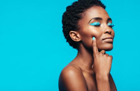 Sluit omhoog van jong vrouwelijk model met trillende make-up tegen blauwe achtergrond. Afrikaanse jonge vrouw aan haar perfecte huid te raken.