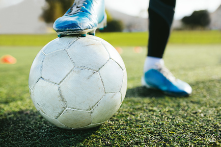 Close up of teenager's legs with a ball on football pitch. Cropped shot of soccer player training on the artificial grass field. Stockfoto
