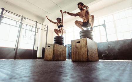 Young athletes box jumping at cross training gym. Fitness man and woman doing a box squat at the gym. Fitness couple doing intense exercise at health club.