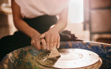 女性・ ポッター三角スクレイピング ツールを使用して陶芸家のホイールを洗浄します。陶器のホイールから粘土を削り写っていた。 写真素材