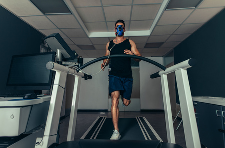 VO2 max test. Fit young man running fast on treadmill with a mask. Athlete examining his performance in sports science lab. Stock Photo