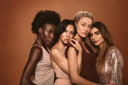grupo de diversos mujeres de pie juntos en el fondo marrón. amigos alegres mujeres alegres que miran la cámara en el estudio