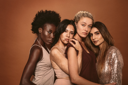 Group of diverse women standing together on brown background. Multi ethnic female friends looking at camera in studio.