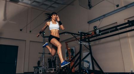 Atleta feminina com sensores de captura de movimento em seu corpo correndo no laboratório biomecânico. Gravando o movimento e desempenho de desportista no laboratório de ciências do esporte.