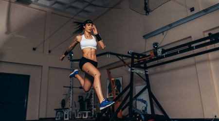 Lekkoatletka z czujnikami ruchu na ciele w laboratorium biomechanicznym. Rejestracja ruchu i wydajności sportsmenki w laboratorium sportowym.
