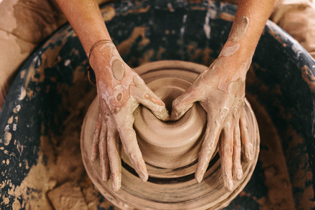 Potter making a clay pot on pottery wheel in workshop. Hands of a craftswoman moulding clay on pottery wheel.
